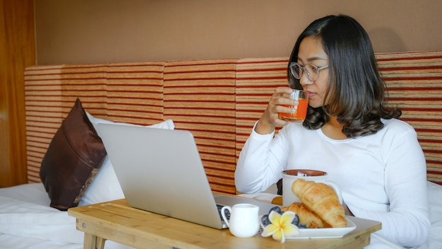 아침 식사를하는 관광객의 사진과 고급 호텔 방, 건강 식품 개념의 침대에서 노트북을 사용했습니다.