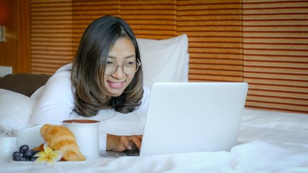 관광객의 사진은 노트북을 사용하고 고급 호텔 방, 건강 식품 개념의 침대에서 아침 식사를 먹었습니다.