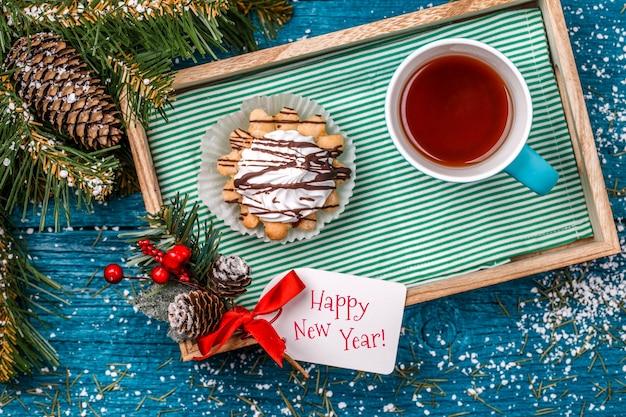 トウヒの枝、雪とクリスマスの装飾、はがきとテーブルの上のお茶とケーキのマグカップとトレイの写真