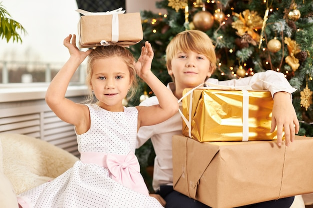 크리스마스 트리에서 포즈를 취하는 두 사랑스러운 유럽 어린이 형제의 그림. 그녀의 머리에 상자와 함께 그 옆에 그의 귀여운 여동생과 함께 새해 선물을 풀고 잘 생긴 십대 소년