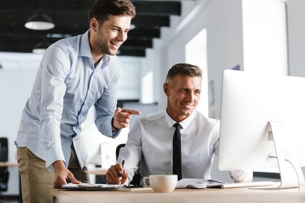 Изображение двух коллег, работающих вместе за компьютером