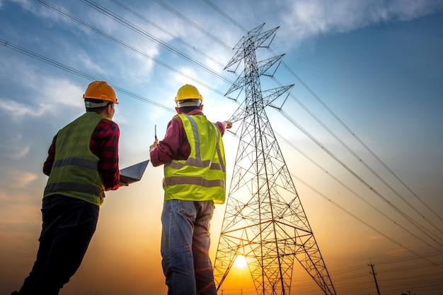 발전소에 서있는 컴퓨터를 사용하여 전기 작업을 점검하는 두 명의 전기 기술자가 고압 전극에서의 계획 작업을 확인하는 그림.
