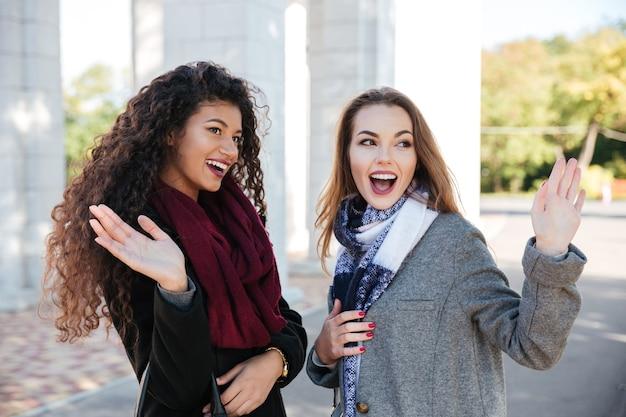 スカーフのコミュニケーションを身に着け、友達に手を振っている2人のゴージャスな若い女性の写真。脇を見てください。