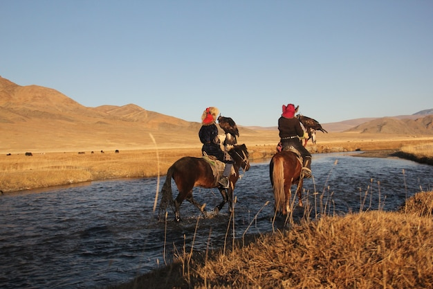丘のある人けのない谷に囲まれた川の2つの乗馬の写真