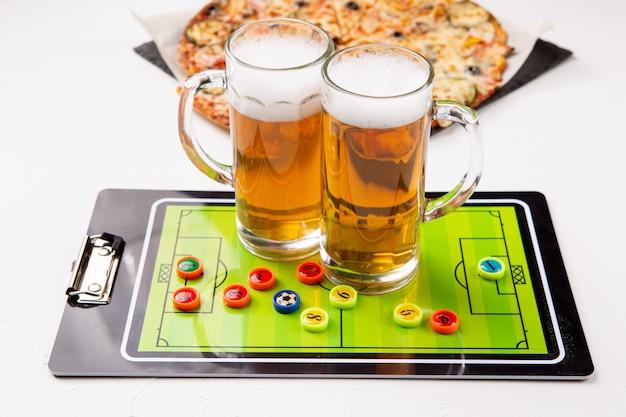 ビール、テーブルフットボール、白いテーブルの上のピザの2つのマグカップの写真