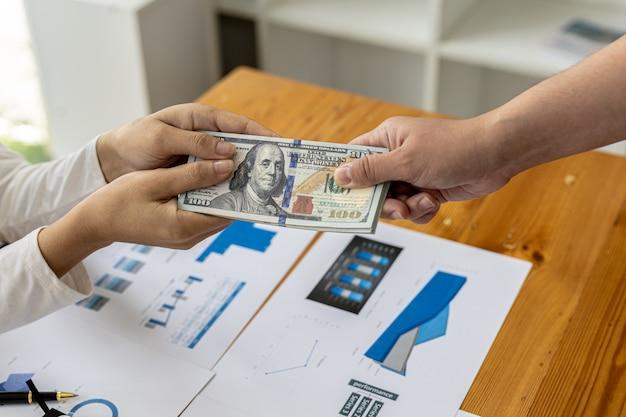 ドルを渡す二人の写真、彼らは違法な相互利益のために彼らに賄賂を贈ることによって腐敗した行動をしているビジネスパートナーです。ビジネス詐欺と賄賂の概念。