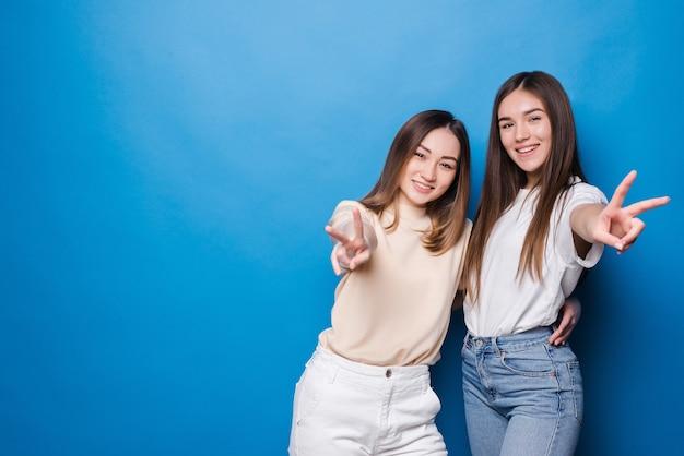 一緒に立って青い壁に平和のジェスチャーを示している2人の遊び心のある女の子の写真