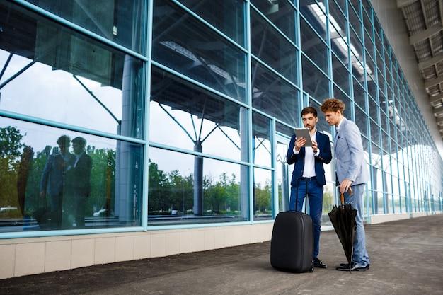 Изображение двух молодых бизнесменов, говорить в аэропорту и проведение планшета