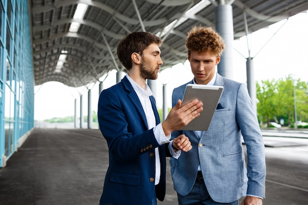 Изображение двух молодых бизнесменов, говорить на станции и держа планшет