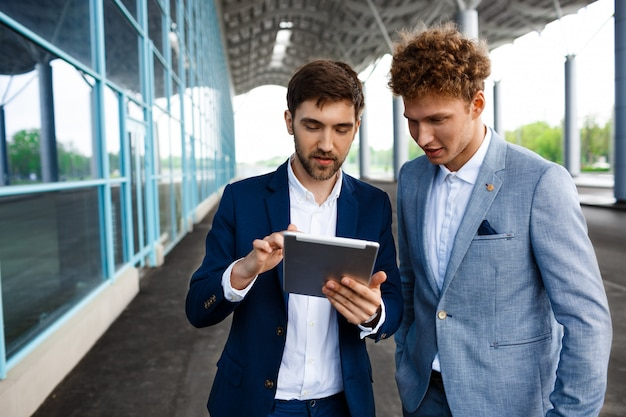 Изображение двух молодых бизнесменов, говорить на терминале и держа планшет