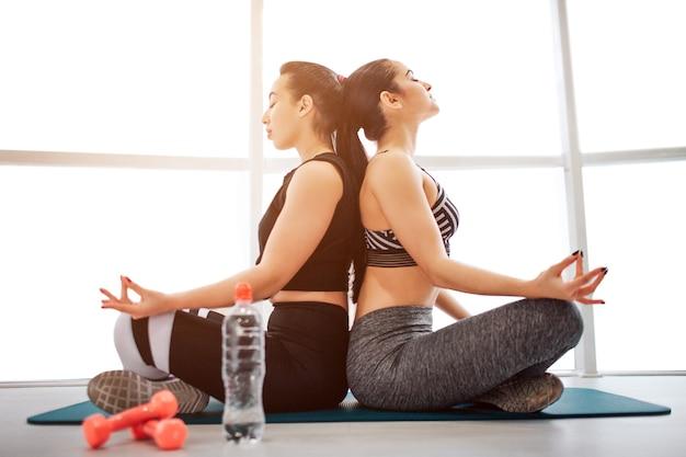 Фотография двух молодых женщин, сидящих спиной к спине в комнате для финтесс