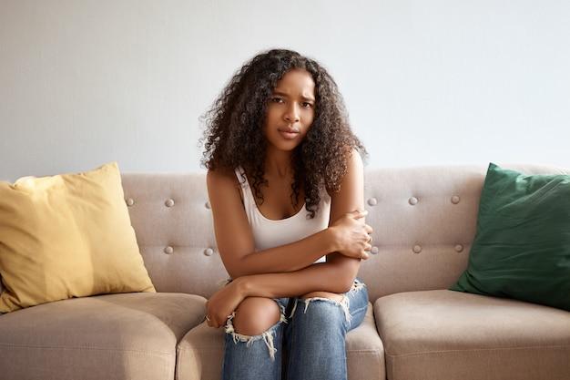 不幸な不機嫌な若いアフロアメリカ人女性の不規則なジーンズと白いトップの写真は、生理があり、けいれんに苦しんで、痛みを伴う表情で見ている彼女の胃に手を置いてソファに座っています