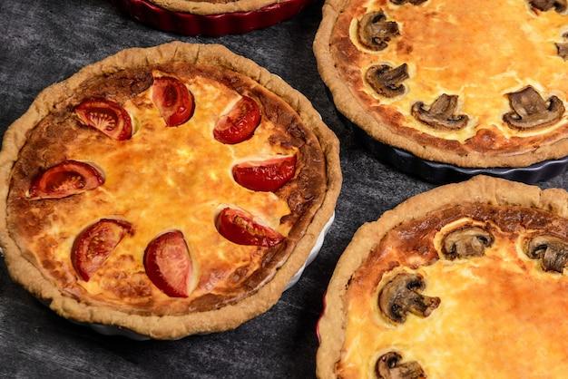 Изображение овощных пирогов с помидорами и грибами на серой поверхности