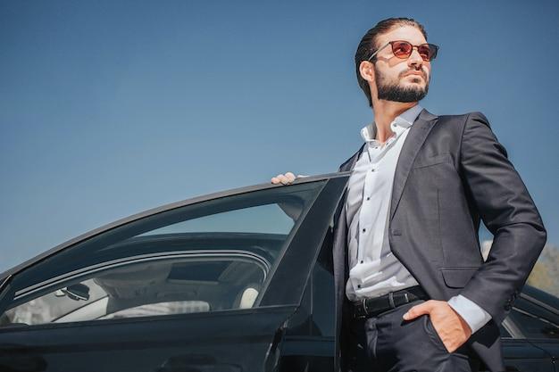 身なりの良いビジネスマンの写真は、ドアを開けた黒い車に立ちます。彼はポケットに1つ、車のドアにもう1つ持っています。若い男のポーズ。
