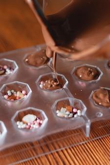 ケーキの準備のためのチョコレートと泡立て器の写真甘いケーキの釉薬ココアを使って自家製のプロセスを溶かして、甘いケーキとチョコレートの釉薬を作成します。