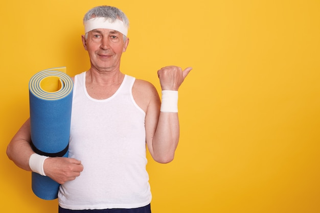 黄色で分離されたスタジオでポーズをとる白い髪のシニア男性の写真