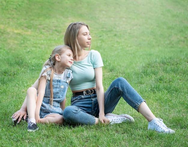 풀밭에 앉아 함께 즐거운 시간을 보내는 여자와 아이의 사진