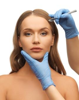 Изображение женского лица и руки косметолога со скальпелем