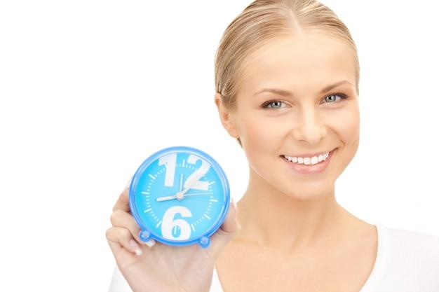 白の上に目覚まし時計を保持している女性の写真