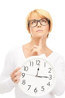 白の上に大きな時計を保持している女性の写真