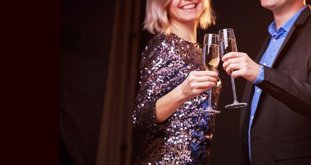 鮮やかなドレスを着た女性と黒の背景にシャンパンとワイングラスを持つ男性の写真