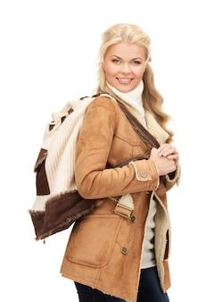 バックパックとシープスキンジャケットの女性の写真