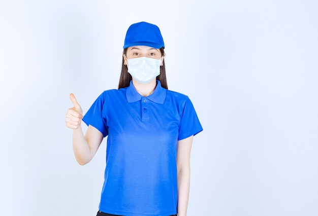 親指を上に見せている制服と医療マスクの女性の写真。