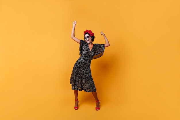 여자 즐겁게 비명과 오렌지 배경에 춤의 그림. 얼굴 아트가있는 폴카 도트 드레스의 소녀는 높은 정신으로 포즈를 취합니다.