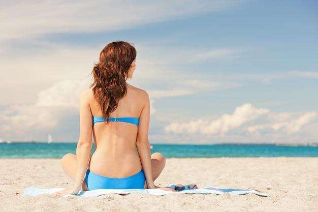 Изображение женщины практикующих позу лотоса йоги на пляже.