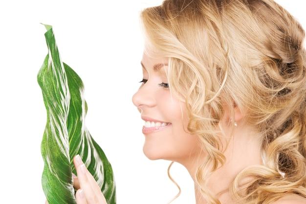 白の上に緑の葉を持つ女性の写真