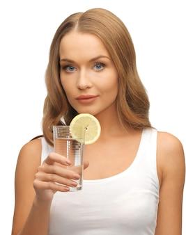 Изображение женщины с долькой лимона на стакан воды.