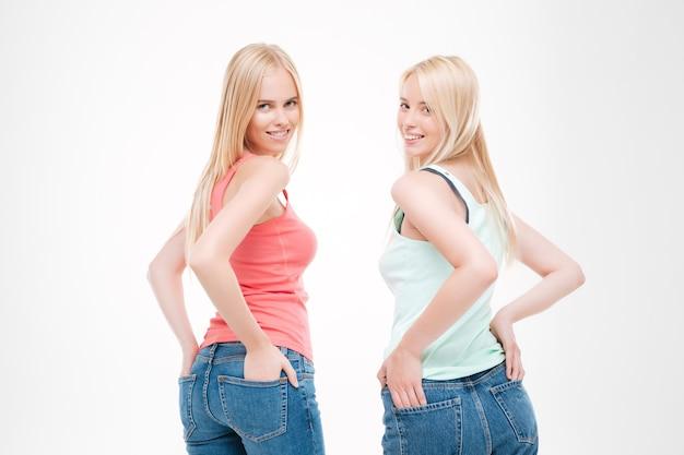 Tシャツとジーンズのポーズを着た女性の写真。白い壁に隔離。正面を見てください。