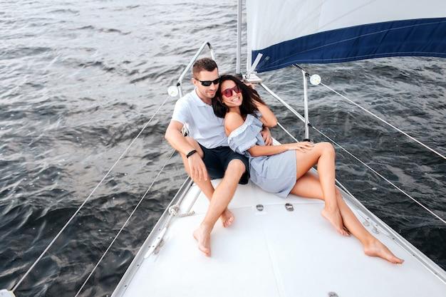 ヨットの船首に座って横たわっている若くて美しいカップルの写真。彼らはサングラスをかけています。彼女はカメラを見てポーズをとっている。ブルネットの笑顔。彼は足を組んで座って楽しみにしています