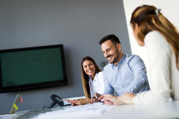 Картина молодых архитекторов, обсуждающих в современном офисе