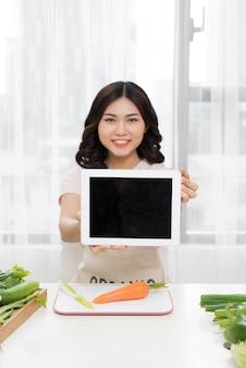 キッチンでタブレットを持つ若いアジアの女性の写真