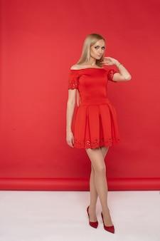 ファッショナブルな服の笑顔と赤と白の背景で隔離のパーティーの準備ができて若い美しい女性の写真