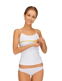 彼女の胸を測定する若い美しい女性の写真
