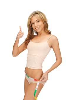 그녀의 엉덩이를 측정하는 젊은 아름다운 여성의 사진