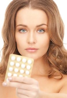錠剤を持つ若い美しい女性の写真