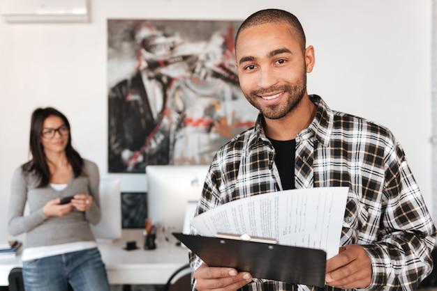 屋内の若いビジネスパートナーの写真。クリップボードを持ってカメラを見てアフリカ人。人に焦点を当てます。