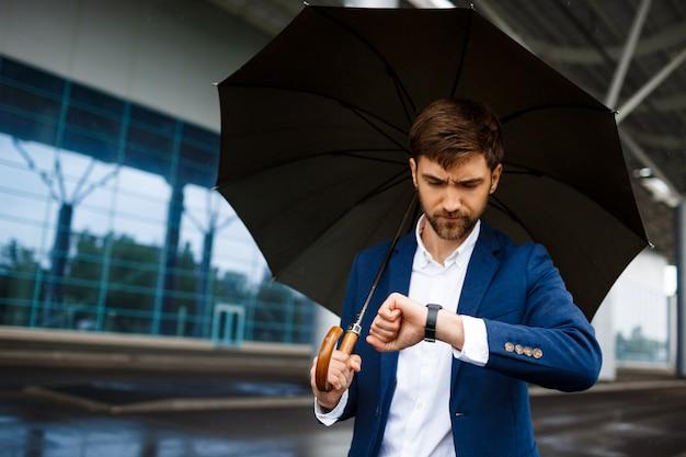 Картина молодой бизнесмен, держа зонтик и глядя на часы в дождливый терминал