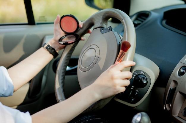 渋滞で車を運転しながら化粧をしている若い実業家の写真。