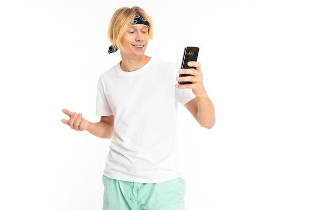 Фотография молодого кавказца со светлыми волосами, в шортах и белой футболке, серфингом в интернете со своим телефоном