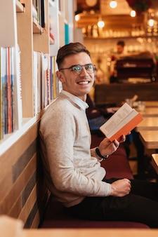 Изображение молодого веселого красивого человека, сидящего в кафе во время чтения книги и взгляда на камеру.