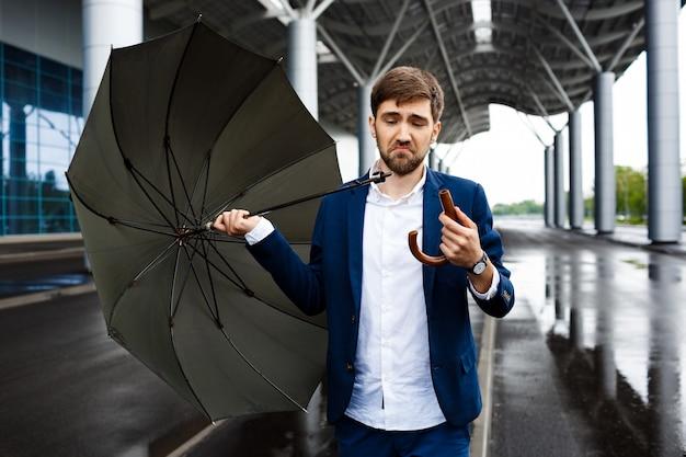 Картина молодой путать бизнесмен на улице, держа сломанной зонтик
