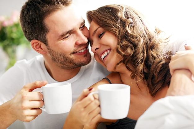 ベッドでコーヒーを飲む若いカップルの写真