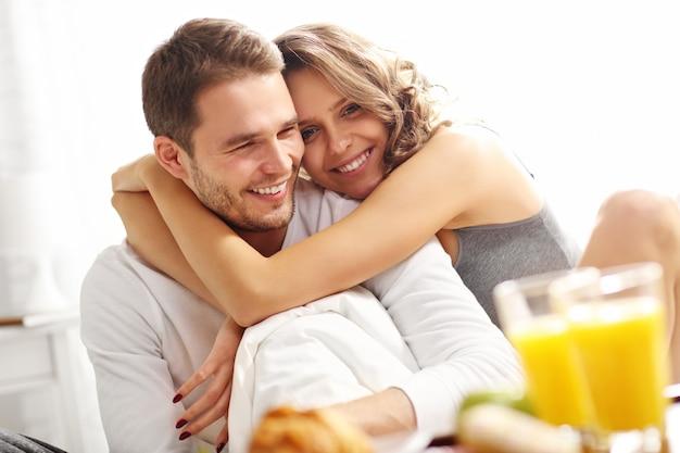 Изображение молодой пары, завтракающей в постели