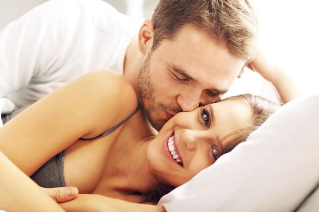 ベッドでキスしている若いカップルの写真
