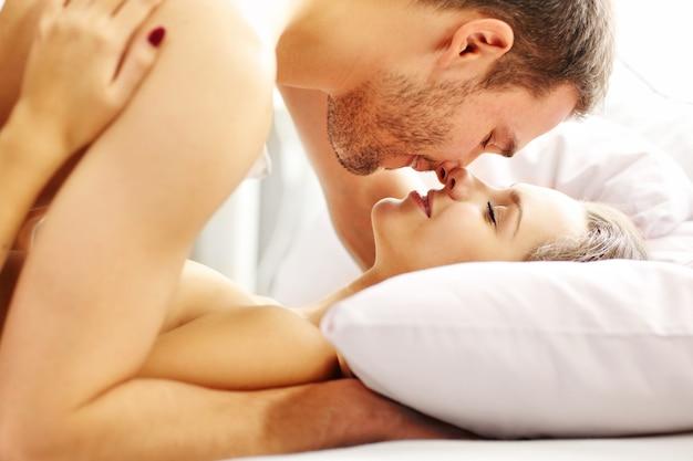 침대에서 키스하는 젊은 부부의 사진