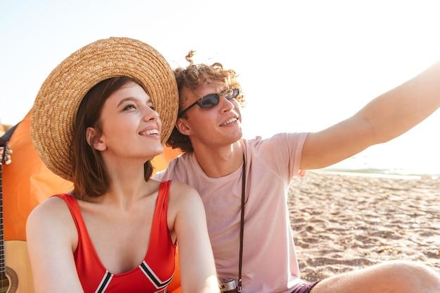 脇を見て屋外のビーチに座っている若いかわいい愛情のあるカップルの友人の写真